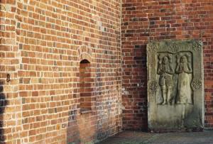 Der Harmelingk-Stein neben dem Kirchturm – links der Ring für das Halseisen